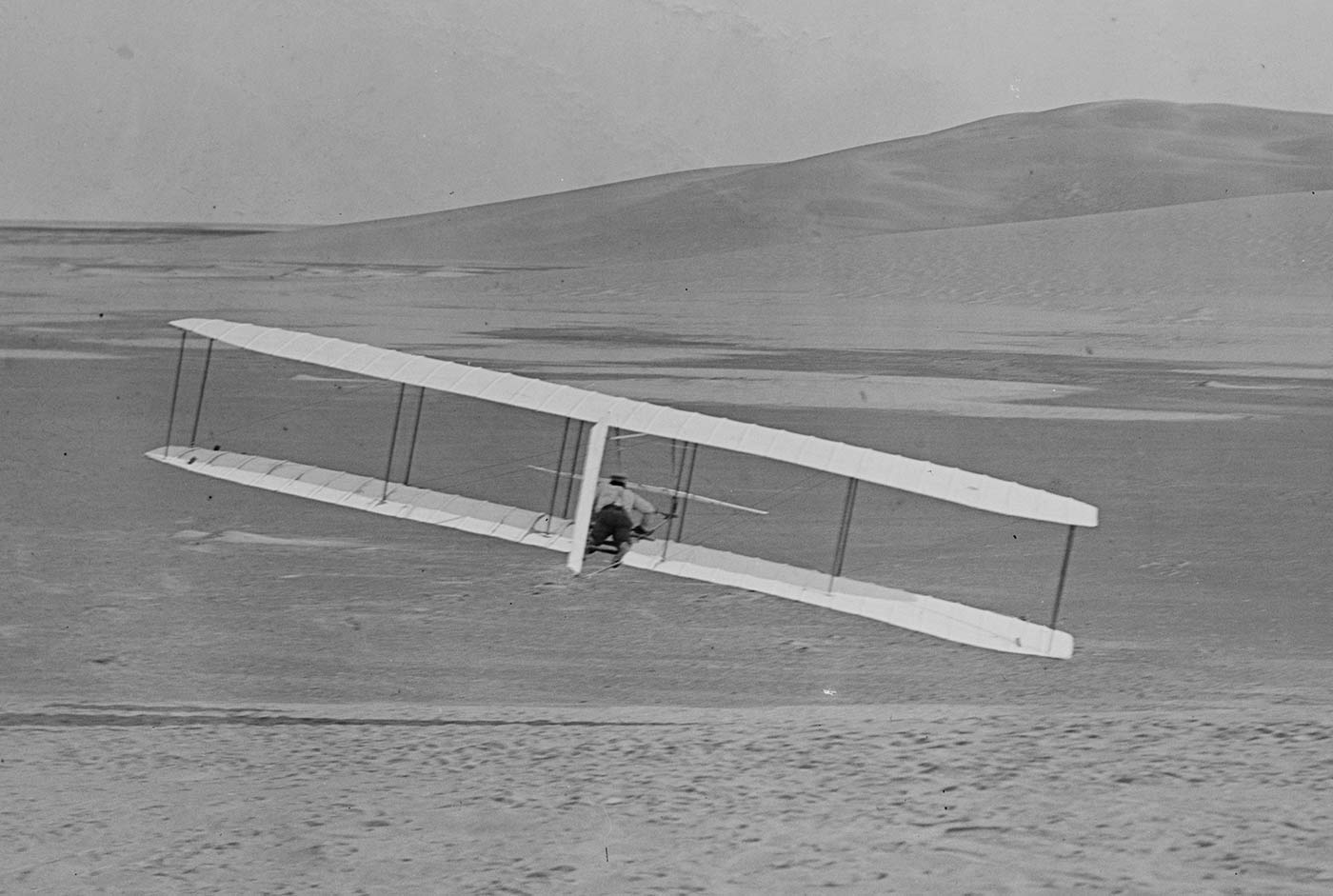 Rear view of Wilbur Wright making a right turn with the Wright Glider, 1902.