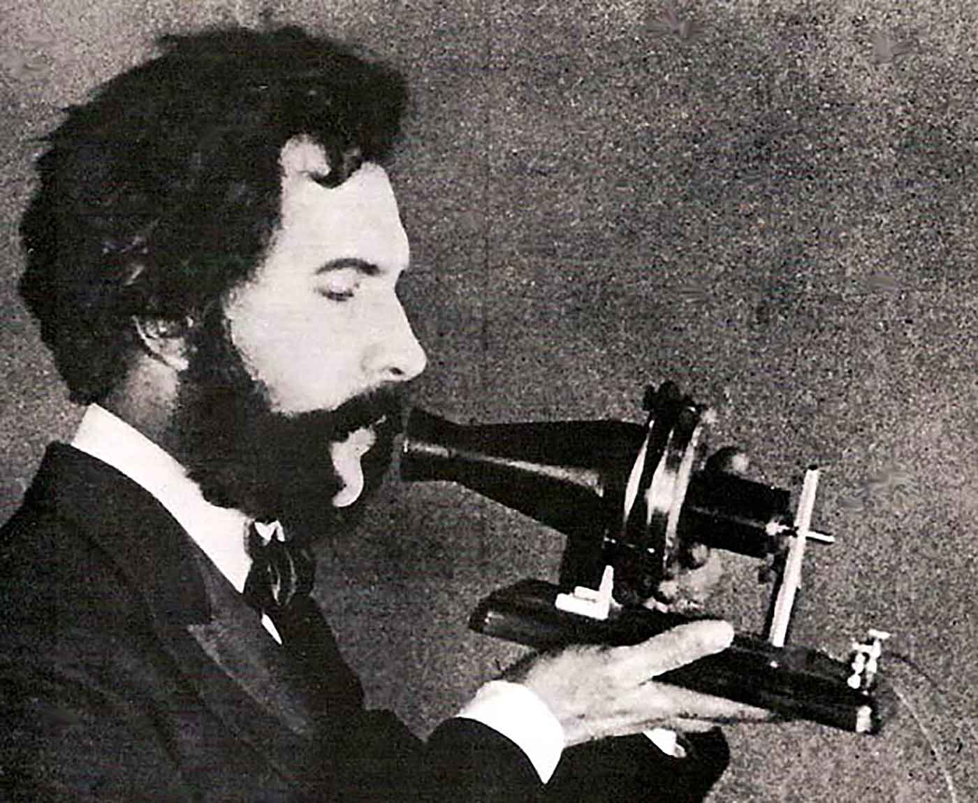 An actor portraying Alexander Graham Bell speaking into a early model of the telephone for a 1926 promotional film by the American Telephone & Telegraph Company (AT&T).