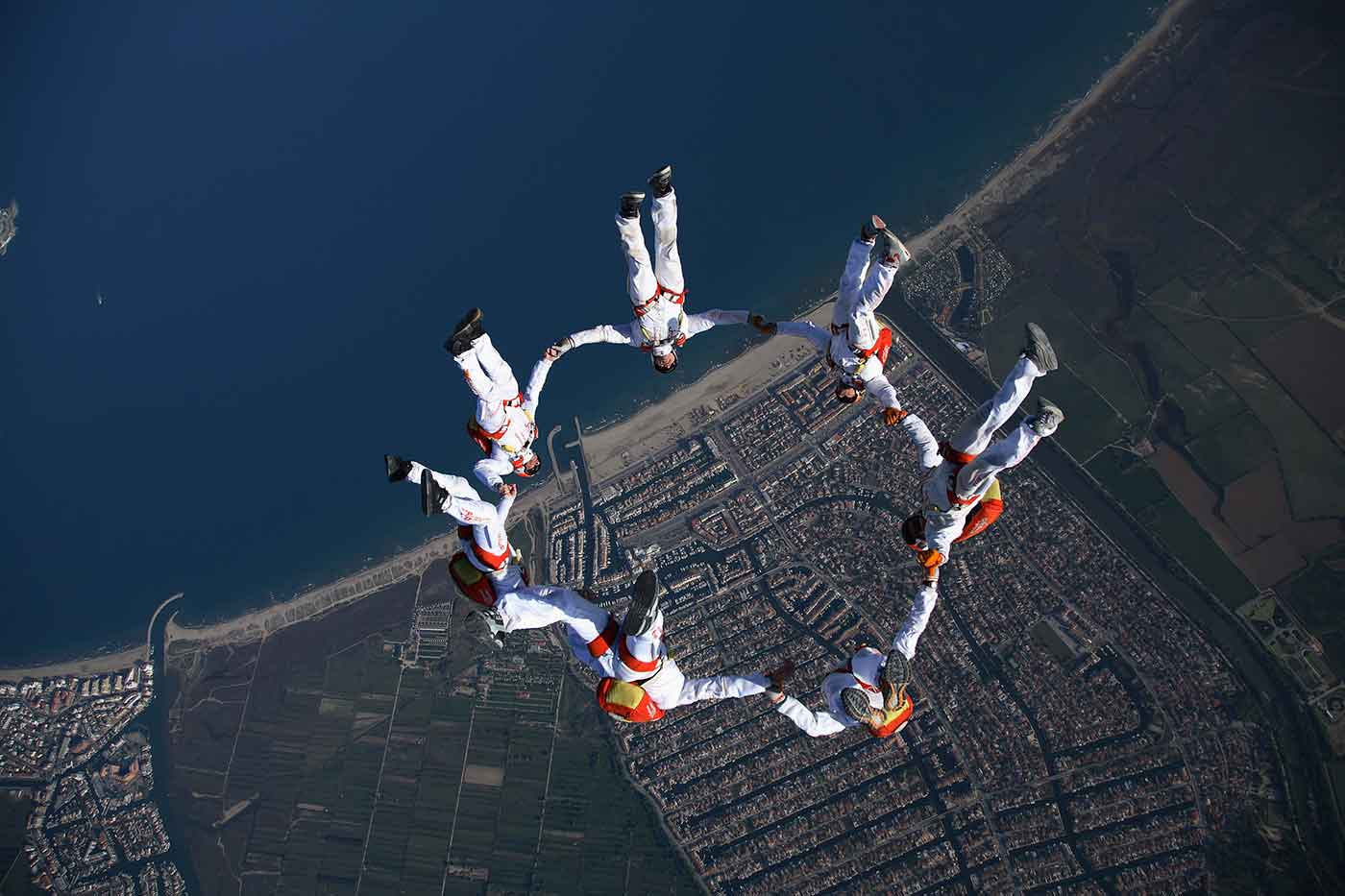 Photo of skydivers forming a circle in the air