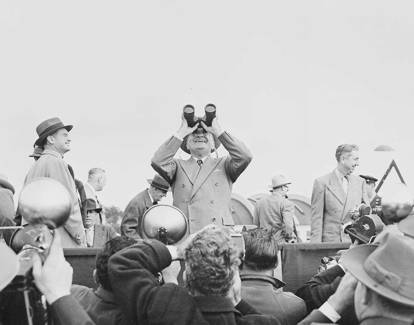 Photograph of President Truman using binoculars to observe an aerial display during an air show at Andrews Air Force