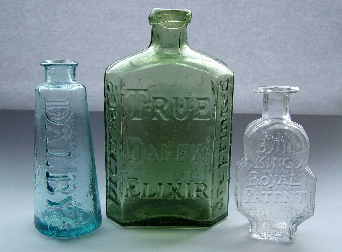Three antique medicine bottles.