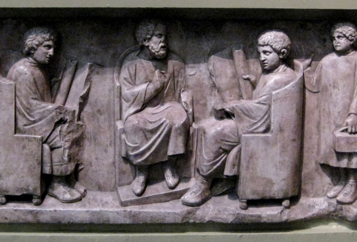 Relief found in Neumagen near Trier, a teacher with three discipuli. Around 180–185 CE. Photo of casting in Pushkin museum, Moscow.