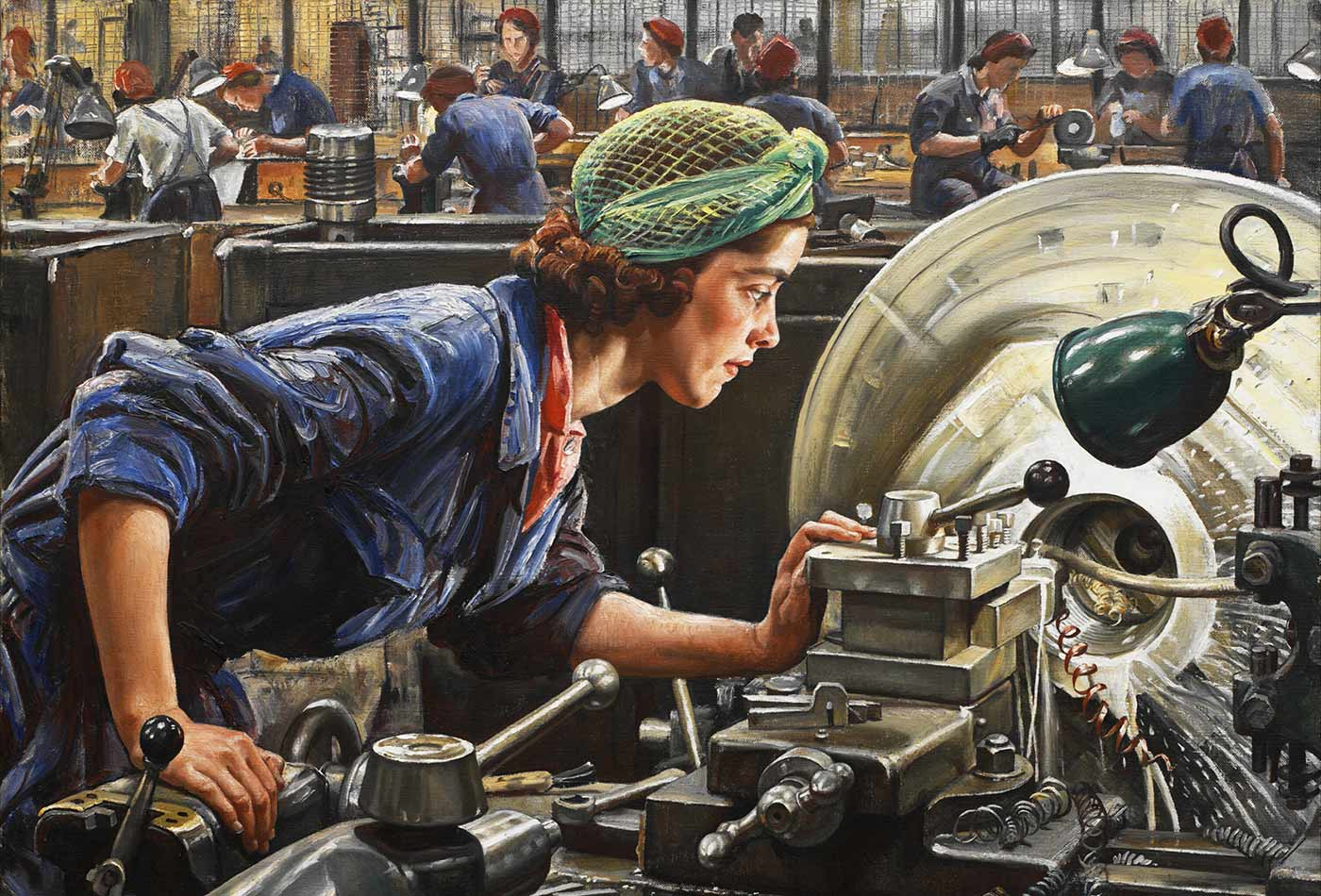 A young factory worker at work on an industrial lathe.