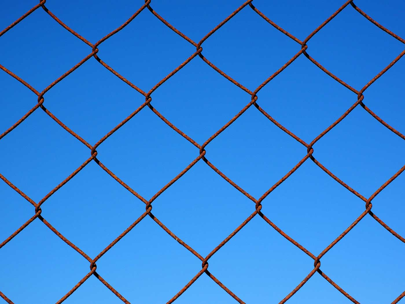 Wire fence against a blue sky
