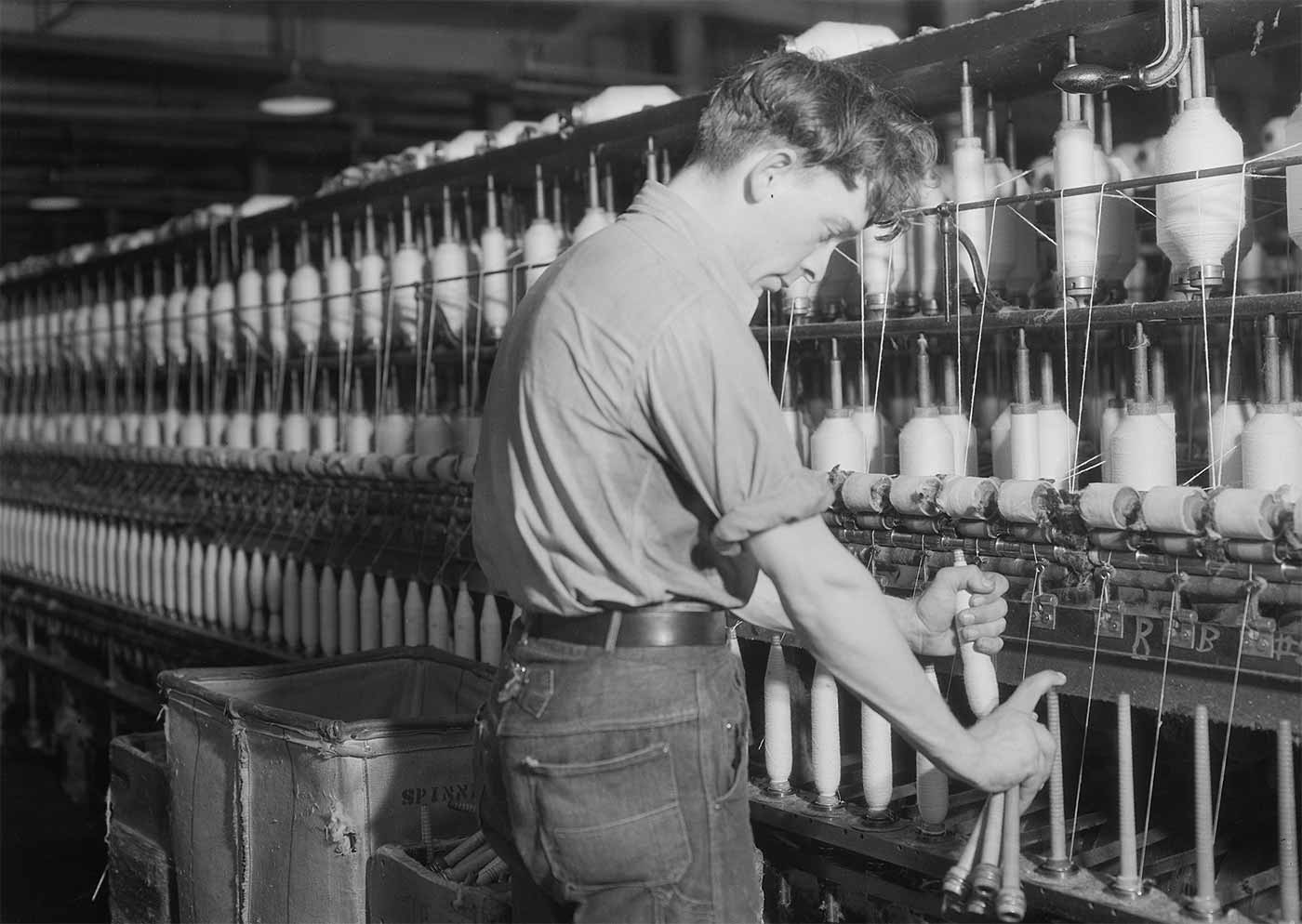 Man fixing machine at Millville Manufacturing Co.