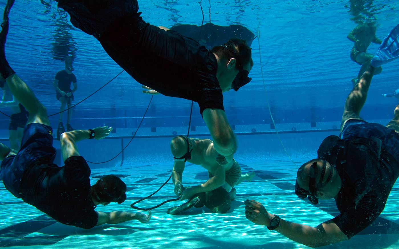 Instructors watch a tudent demonstrate knot-tying skills during water proficiency training.