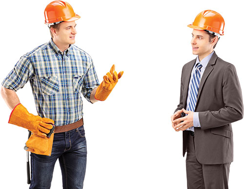 Photo shows Daniel and Stefan wearing construction helmets and talking to each other.