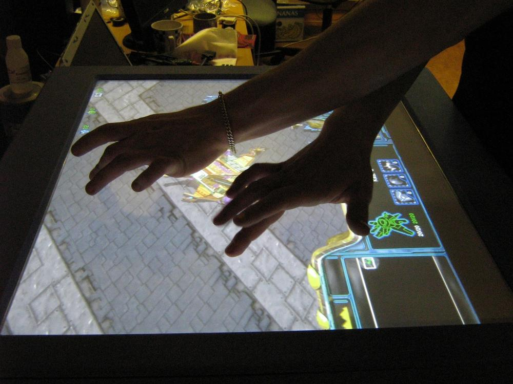 Designers experimenting with a multitouch system to play Starcraft with two hands. Courtesy Harry van der Veen and Natural User Interface.