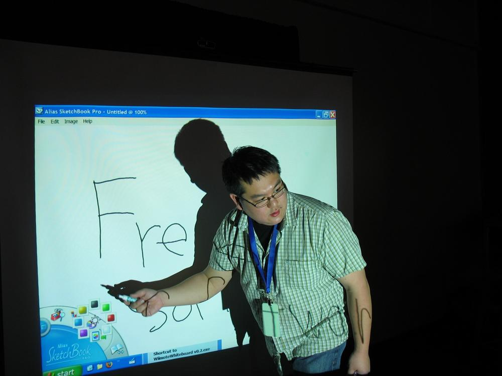 "Johnny Chung Lee demonstrating one of his infamous Wiimote hacks at the 2008 Maker Faire. Using an infrared ""pen,"" users can, by pointing, select different drawing instruments and turn any wall into a virtual whiteboard. Courtesy Sebastian Heycke."