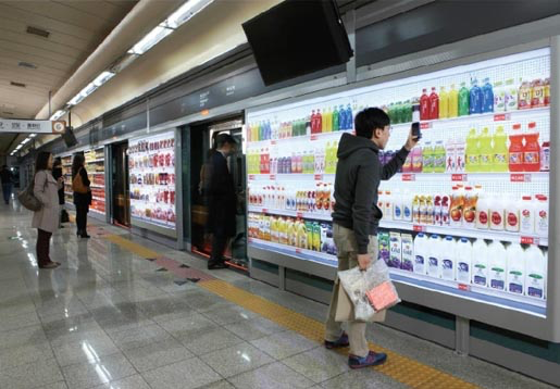 Commuter shopping Home Plus's virtual supermarket shelves (image: http://theinspirationroom.com/daily/2011/homeplus-virtual-subway-store)