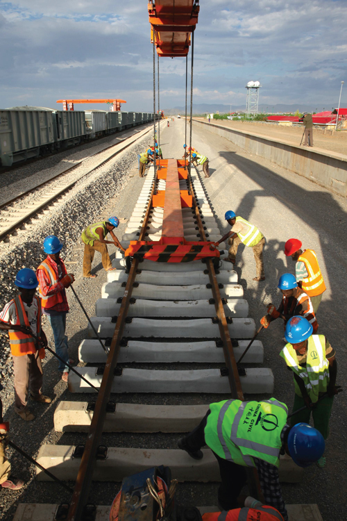 Workers wearing hard hats and reflective vests construct the concrete bed of an electric railway.