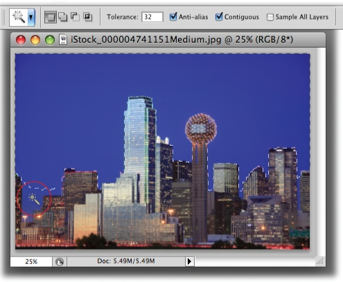 With its tolerance set to 32, the Magic Wand did a good job of selecting the sky behind downtown Dallas.You've got several ways to select the spots it missed like the area circled at the bottom left: You can add to the selection by pressing the Shift key as you click in that area, increase the tolerance setting in the Options bar and then click the sky again to create a new selection, or skip to page 154 to learn how to expand your selection with the Grow and Similar commands.