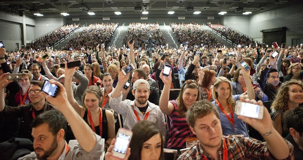 Conference attendees at SXSW Interactive Festival show their phones (photo by Kris Krug).