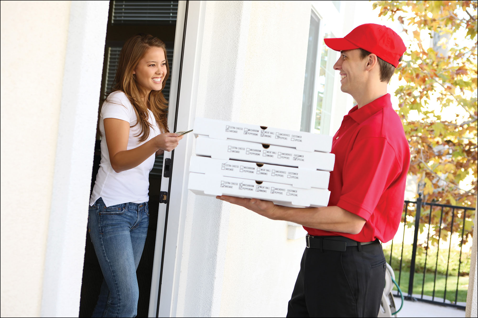 Photo of a pizza delivery man delivering a stack of pizzas to a customer's home