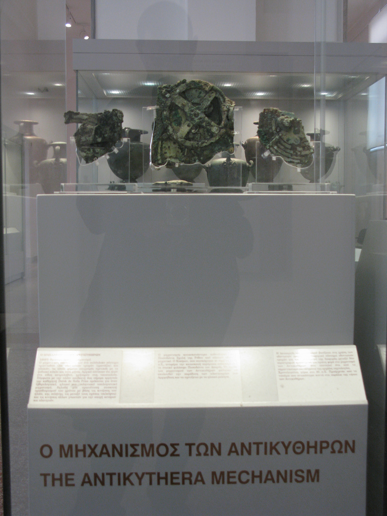 Photographic image of The Antikythera Mechanism exhibit at the National Archeological Museum of Athens. Grecian urns are on display in the background.