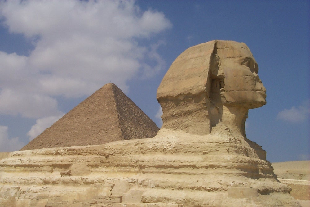 Image of The Great Sphinx at Giza with upper half of the Great Pyramid in the background.