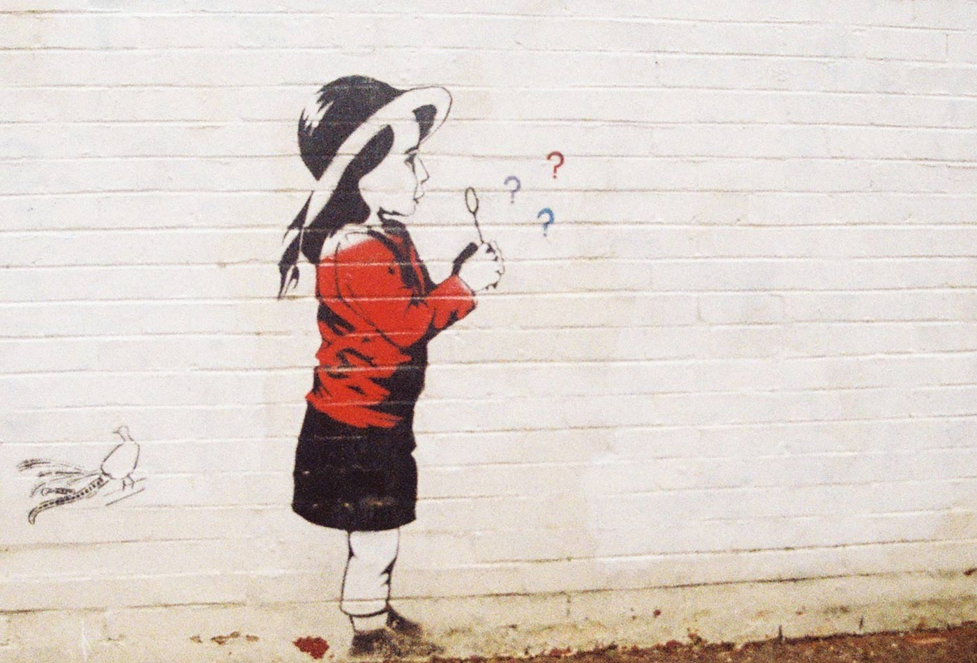 Painting on wall of girl blowing question marks.