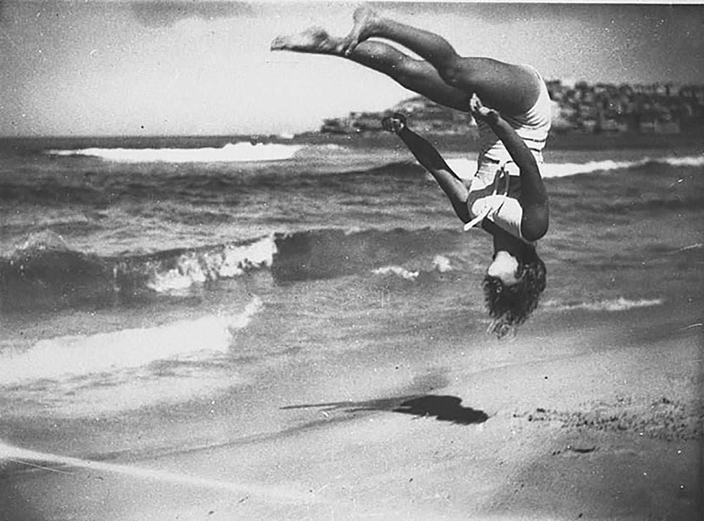 Peggy Bacon in mid-air backflip, Bondi Beach, Sydney, 6/2/1937 / by Ted Hood.