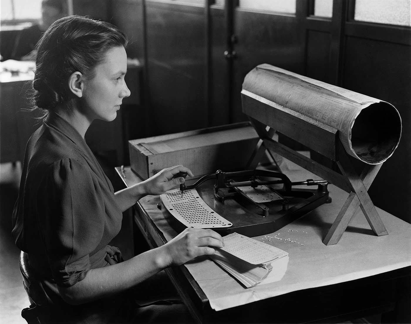 A woman posed with a Hollerith pantograph: the keyboard is for the 1920 population card, and a 1940 census form.