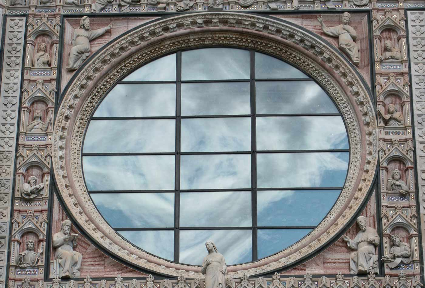 Cathedral (Duomo) of Siena, clouds reflected in the rose window in the West façade.