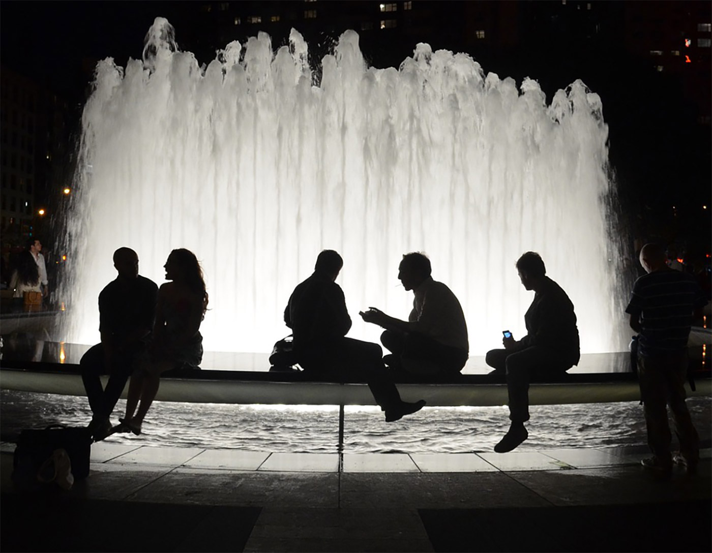 People talking in front of a fountain
