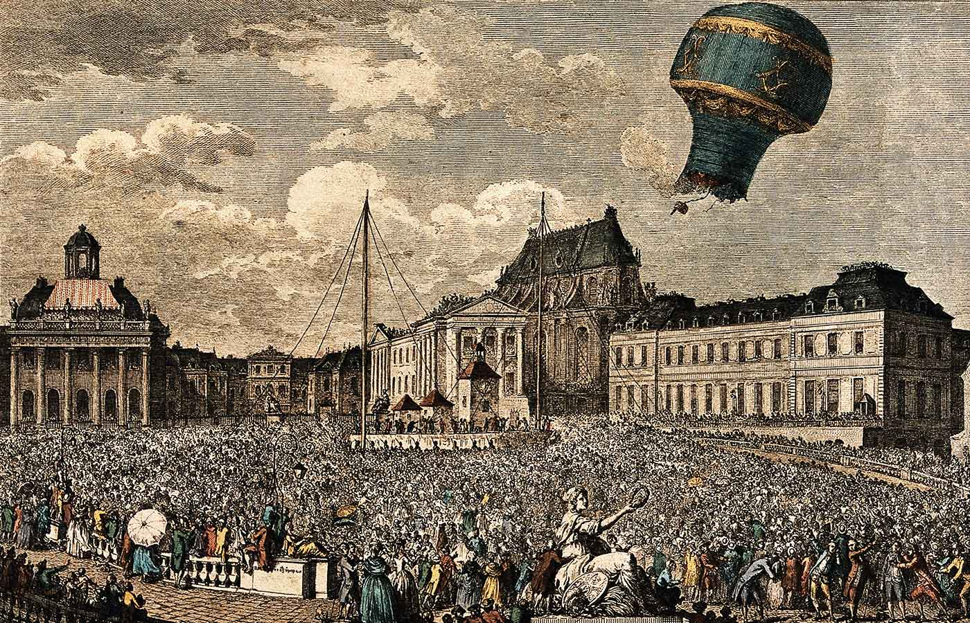 A crowd watches from the streets as a hot-air balloon takes off