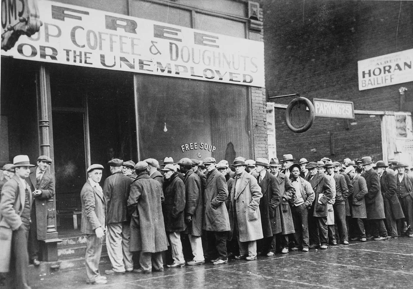 Unemployed men queued outside a depression soup kitchen opened in Chicago by Al Capone.